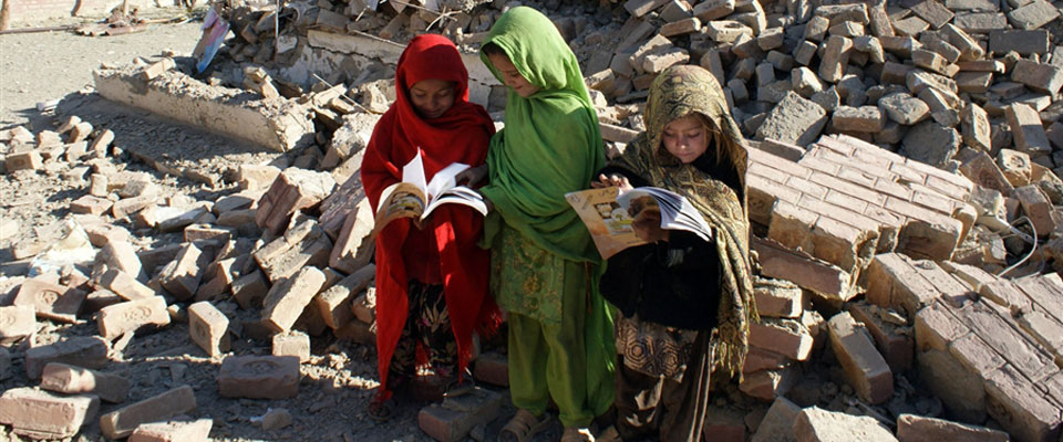 Pakistani schoolgirls collect their books from the debris of a government girls' school near the Afghan border in the Bara area of Khyber Agency, Pakistan on Jan. 24 2011